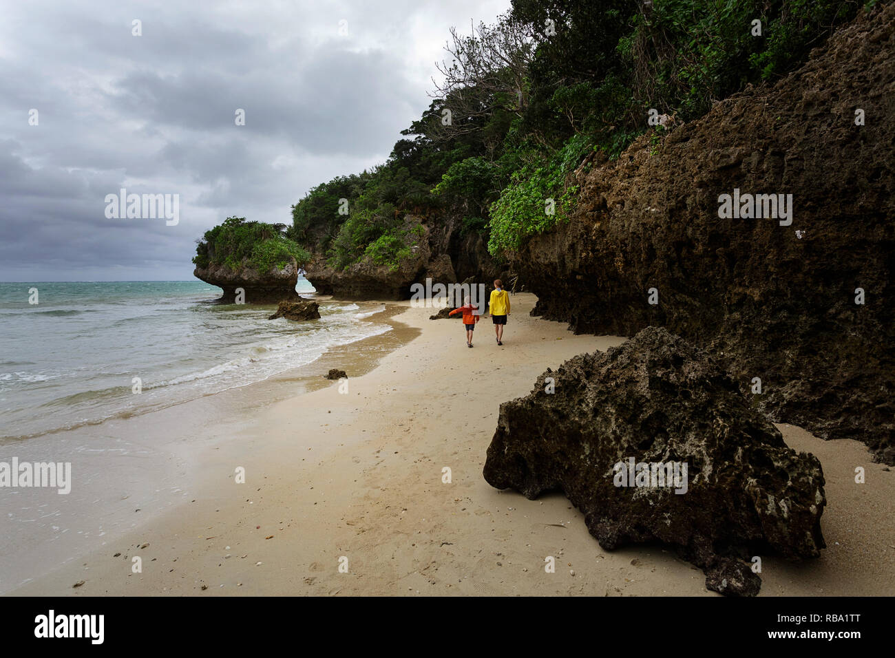 Mother and son walking on dramatic sandy beach with limestone scultures at Ibaruma Sabichi Cave, Ishigaki, Japan Stock Photo