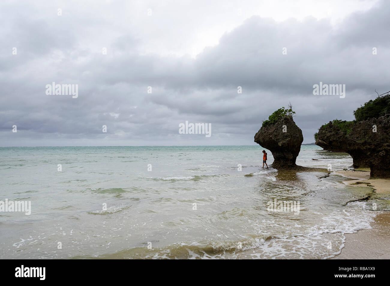 Young boy standing under limestone sculpture by the sea at sandy beach at Ibaruma Sabichi Cave, Ishigaki, Japan Stock Photo