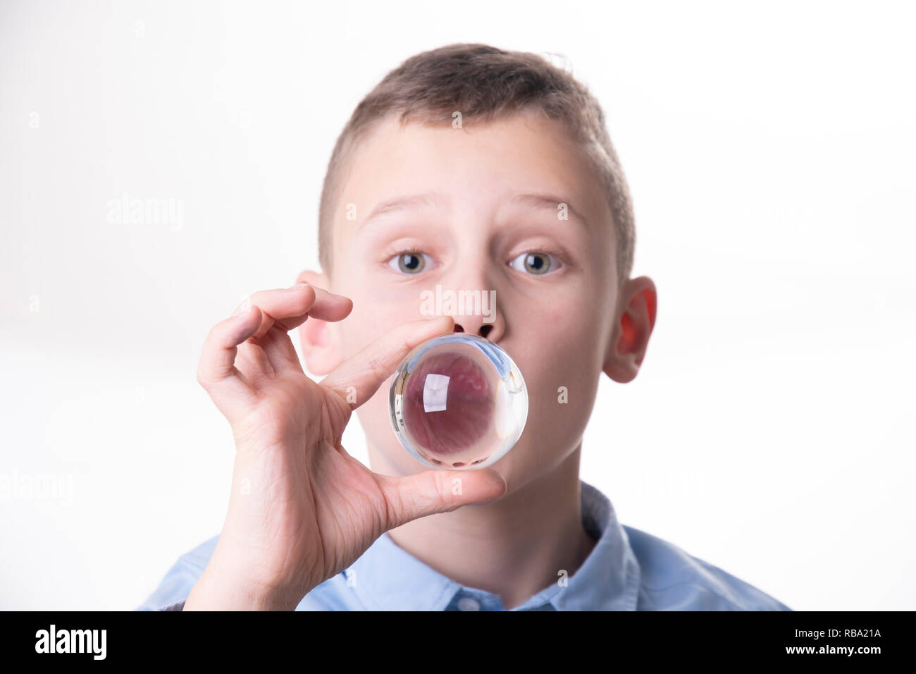 Future - boy breathes into a glass ball directly in front of his mouth isolated on white background Stock Photo