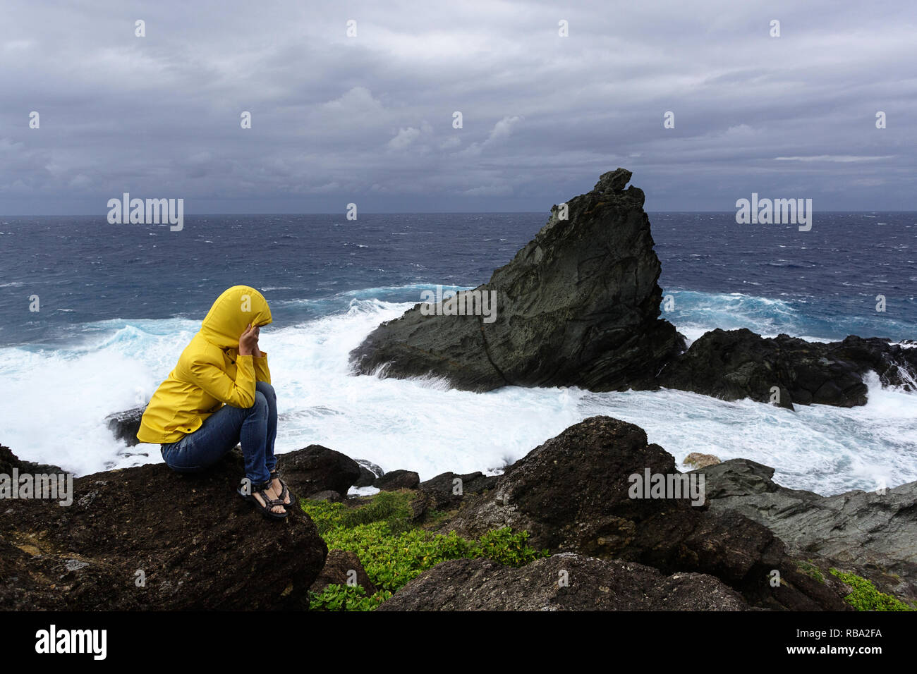 Woman in yellow jacket freezing on a rock looking at rough