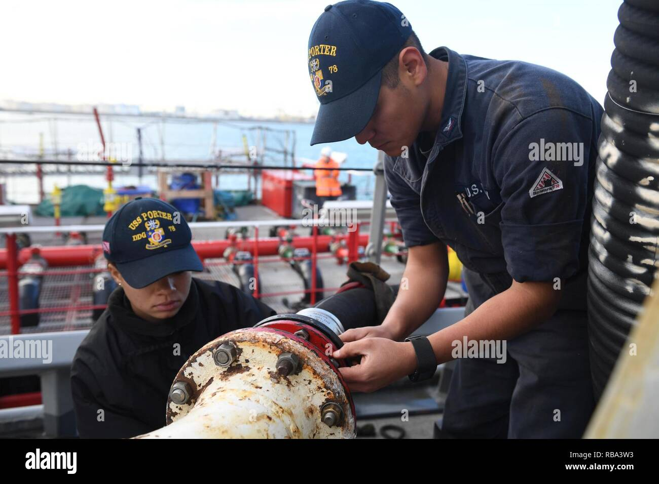 VALENCIA, Spain (Dec. 20, 2016) Petty Officers 3rd Class Giana Hardin, left, and Enrique Gonzalez connect a fuel line to the guided-missile destroyer USS Porter (DDG 78) as it prepares to take on fuel pier-side in Valencia, Spain. Porter, forward-deployed to Rota, Spain, is conducting naval operations in the U.S. 6th Fleet area of operations in support of U.S. national security interests in Europe. Stock Photo