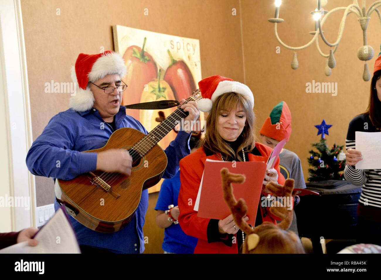 Delia Colvin, Army veteran and international bestselling author, and friend Steven Gary, guitarist and vocalist, perform Christmas carols for children and their families Dec. 20, 2016 at the Fisher House, Travis Air Force Base, Calif. The Travis Fisher Houses are part of a collection of homes built on military bases to provide a place for families in need to stay without charge when a member is hospitalized. - Stock Image