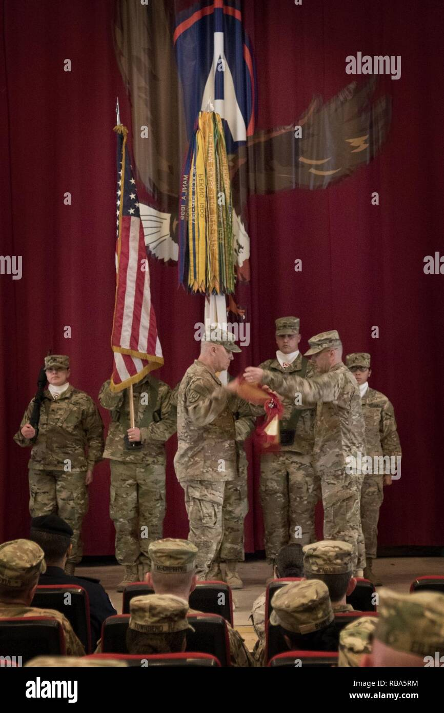 Brig. Gen. Bruce Hackett, the commanding general of the 451st Sustainment Command (Expeditionary), and Command Sgt. Maj. Dennis Thomas, the senior enlisted advisor of the 451st ESC, case their colors during the transfer of authority ceremony to the 316th ESC at Camp Arifjan, Kuwait, Dec. 23, 2016. - Stock Image