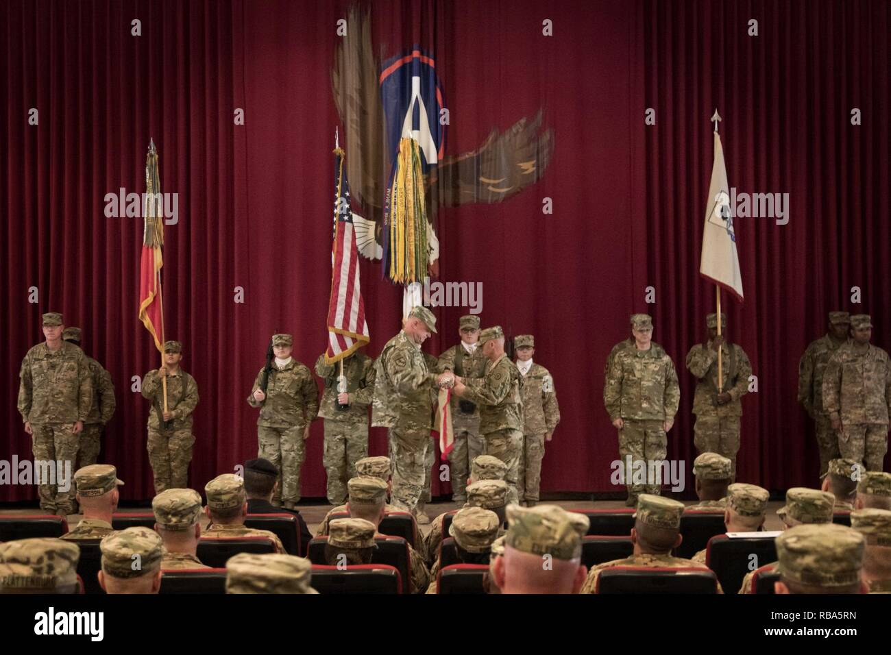 Brig. Gen. Robert Harter, the commanding general of the 316th Sustainment Command (Expeditionary), and Command Sgt. Maj. Johnny McPeek, the senior enlisted advisor of the 316th ESC, uncase their colors during their transfer of authority ceremony from the 451st ESC at Camp Arifjan, Kuwait, Dec. 23, 2016. - Stock Image