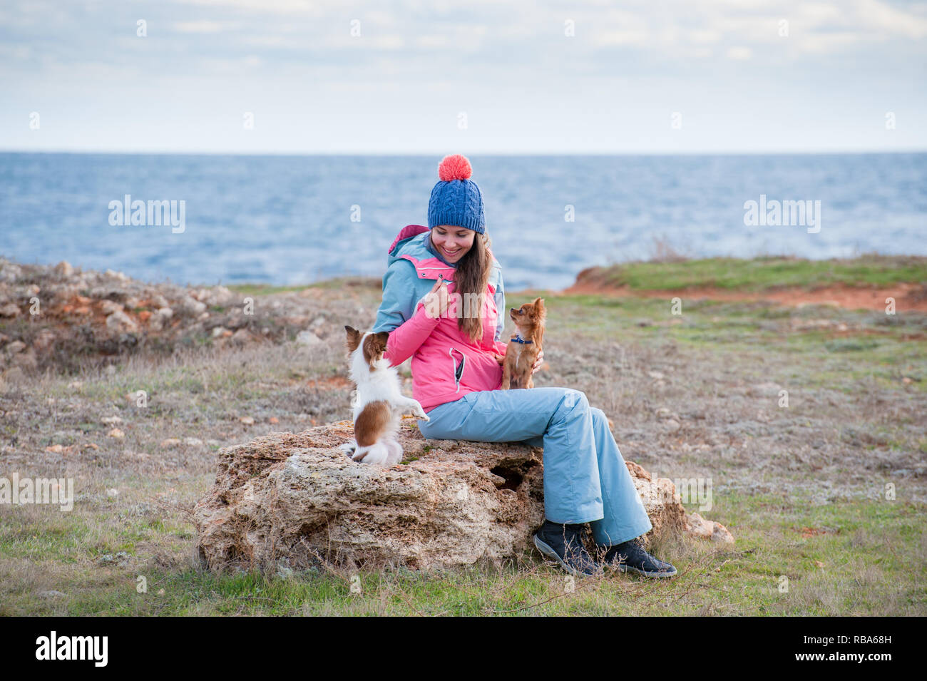 happy smiling beautiful girl in hat track suit sitting on stone with two dogs - Stock Image