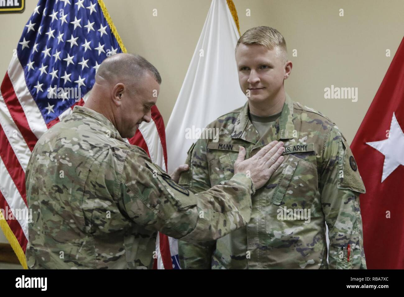 Brig. Gen. Robert D. Harter, 316th Sustainment Command (Expeditionary) commanding general, places the rank of 1st Lieutenant on Christopher Mann during a promotion ceremony at Camp Arifjan, Kuwait, Dec. 31, 2016. - Stock Image