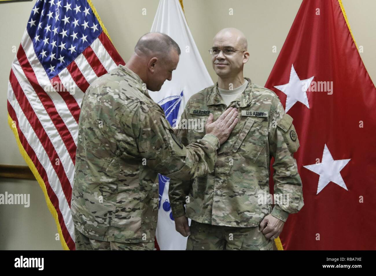 Brig. Gen. Robert D. Harter, 316th Sustainment Command (Expeditionary) commanding general, places the rank of Chief Warrant Officer 4 on Richard Gardner during a promotion ceremony at Camp Arifjan, Kuwait, Dec. 31, 2016. - Stock Image