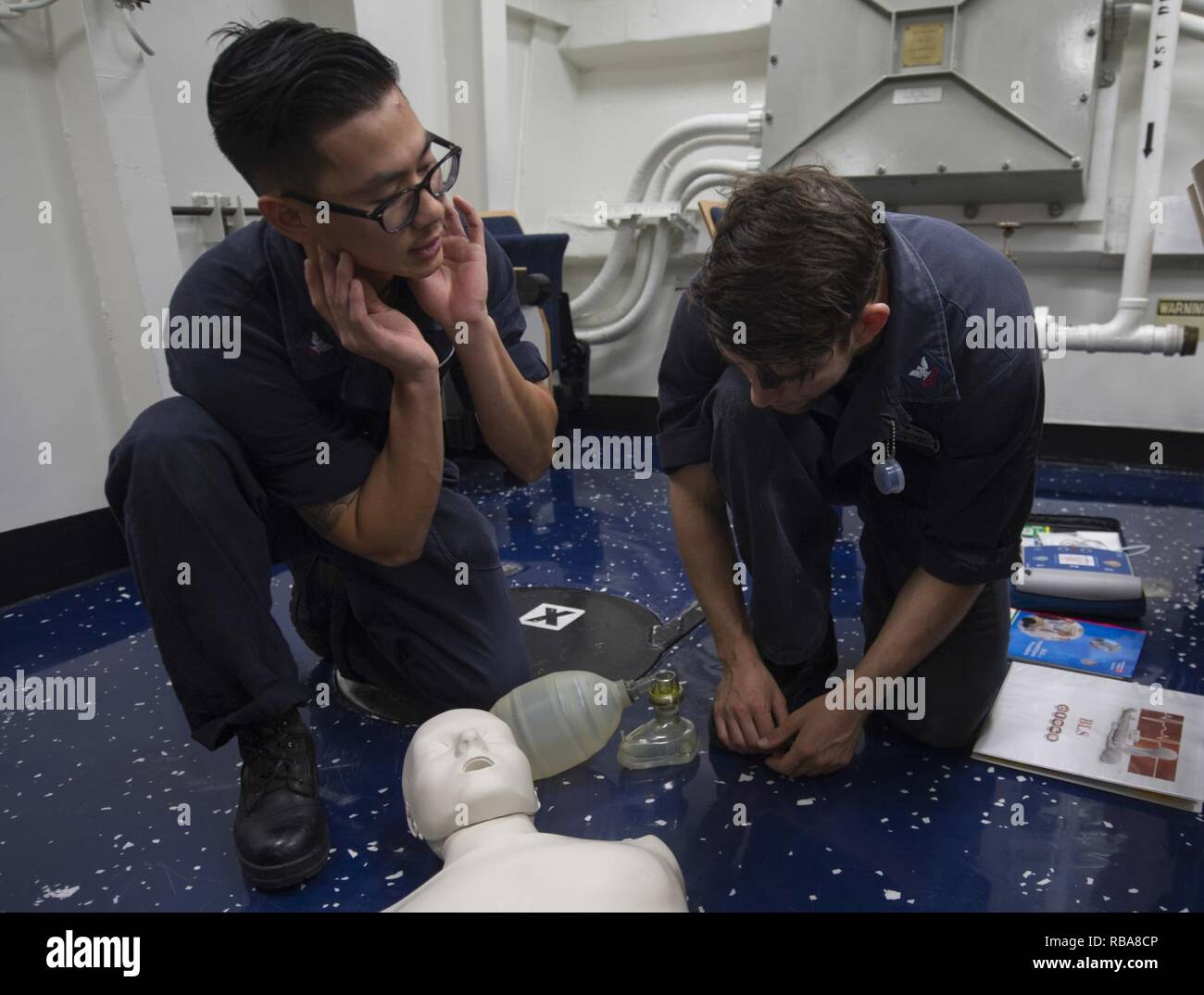 SOUTH CHINA SEA (Jan. 2, 2017) Hospital Corpsman 3rd Class Justin A. Lam, left, teaches Fire Controlman 2nd Class Christopher M. Conley how to perform cardio-pulmonary resuscitation (CPR) during a CPR certification class aboard the Arleigh Burke-class guided-missile destroyer USS John S. McCain (DDG 56). The ship is on patrol in the South China Sea supporting security and stability in the Indo-Asia-Pacific region. - Stock Image
