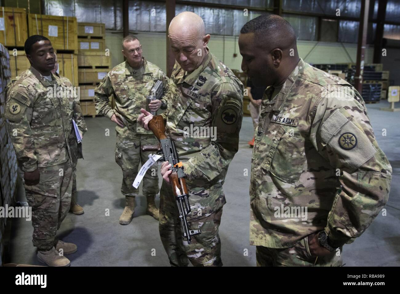U.S. Army Reserve Commanding General, Lt. Gen. Charles D. Luckey, inspects an AK-47 rifle during a tour of the Iraq Train and Equipment Fund (ITEF) warehouse at Camp Arifjan, Kuwait, Jan. 4, 2017. - Stock Image