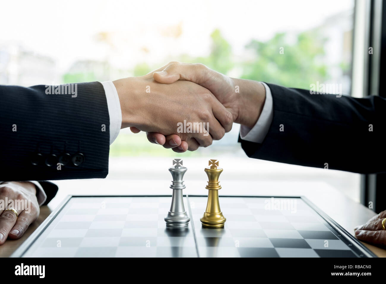 Negotiating business, Two confident business man shaking hands with partners together after finishing up a meeting succeeded Connection Deal Concept - Stock Image