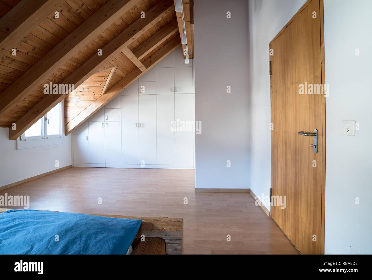bright light modern simple master bedroom with wooden parquet floors and designer closet and traditional wooden beam bed under slanted ceiling in a re - Stock Image
