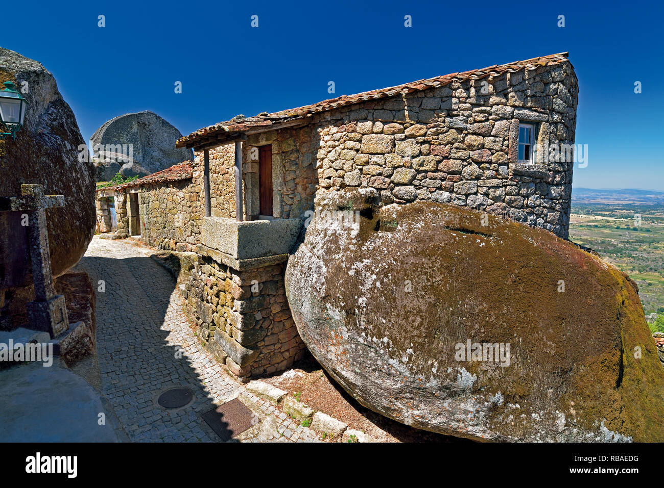 Narrow alley through granite stone houses and huge rocks in historic village Monsanto - Stock Image