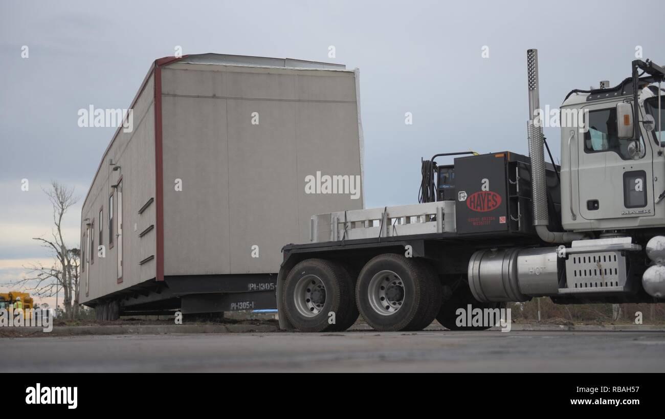 A truck pulls a modular facility into a parking lot Dec  19, 2018 at