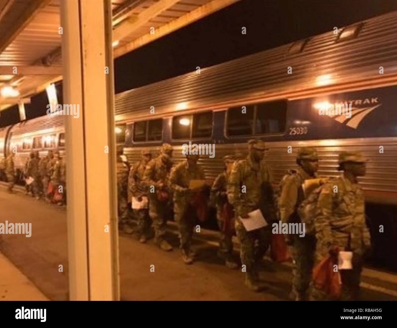 Soldiers training at Fort Jackson, S.C., prepare to board a train at the Columbia Amtrak station for Holiday Block Leave (HBL) early morning Dec. 19, 2018. The 369th Adjutant General Battalion, U.S. Army Soldier Support Institute, provided the mission command at the rail station. Each year during the Christmas and New Year holiday season, U.S. Army Combined Arms Support Command AIT schools conduct HBL to give military students and cadre downtime. - Stock Image