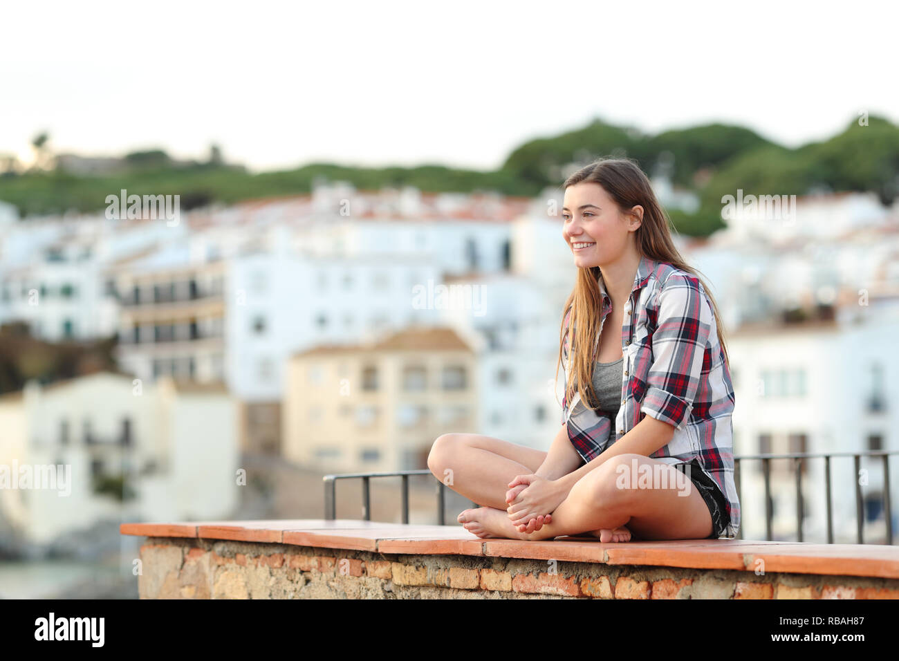 Happy teen contemplating views sitting on a ledge in a coast town on vacation - Stock Image