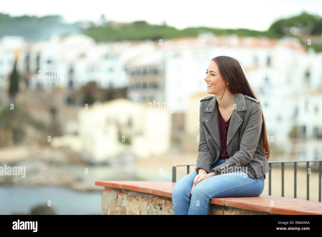 Relaxed woman contemlating views sitting on a ledge in a coast town on vacation - Stock Image