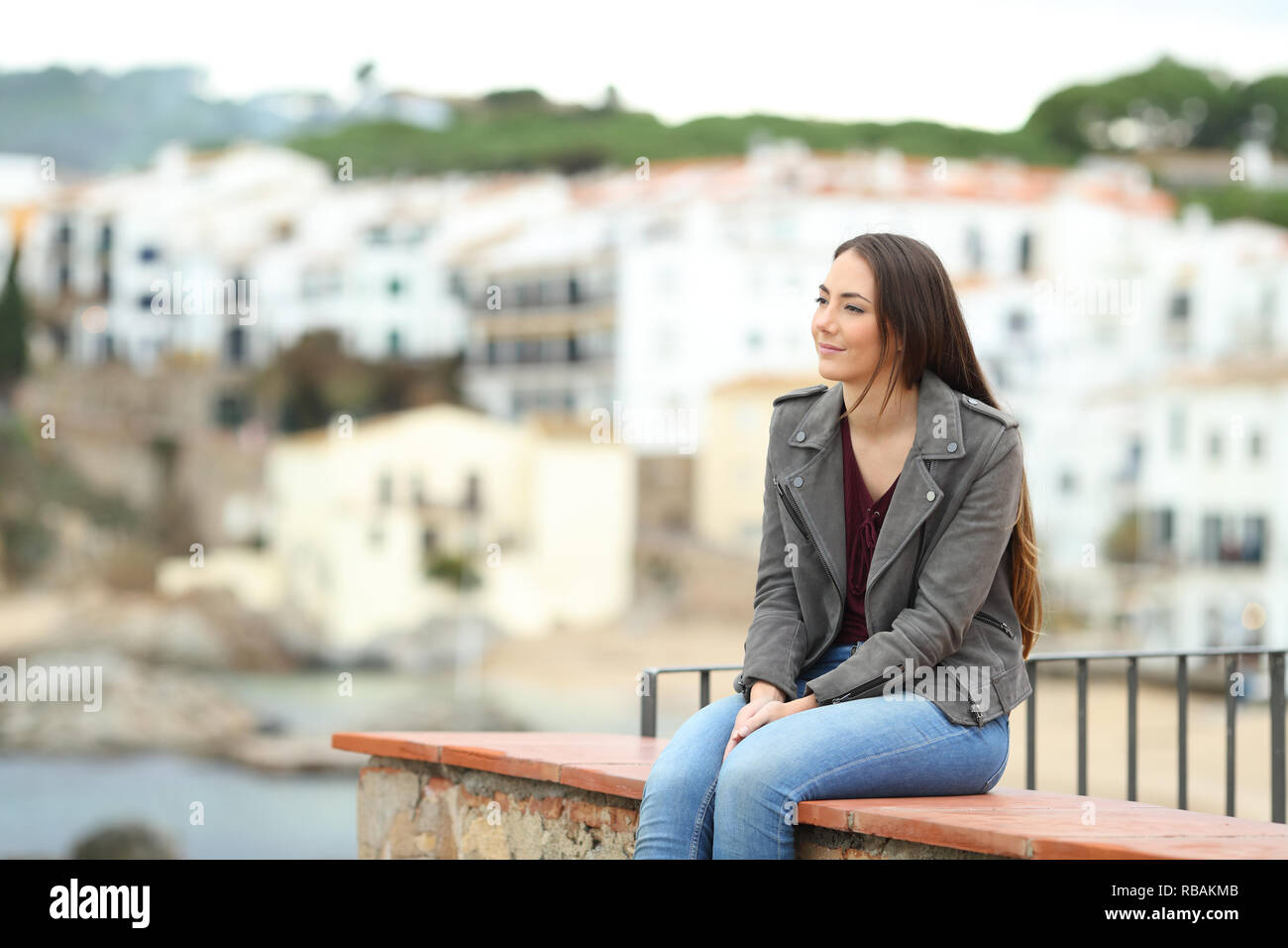 Relaxed woman contemplating views sitting on a ledge in a coast town on vacation - Stock Image