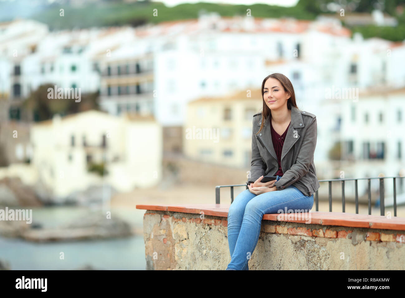 Relaxed woman contemplating ocean from a ledge in a coast town on vacation - Stock Image