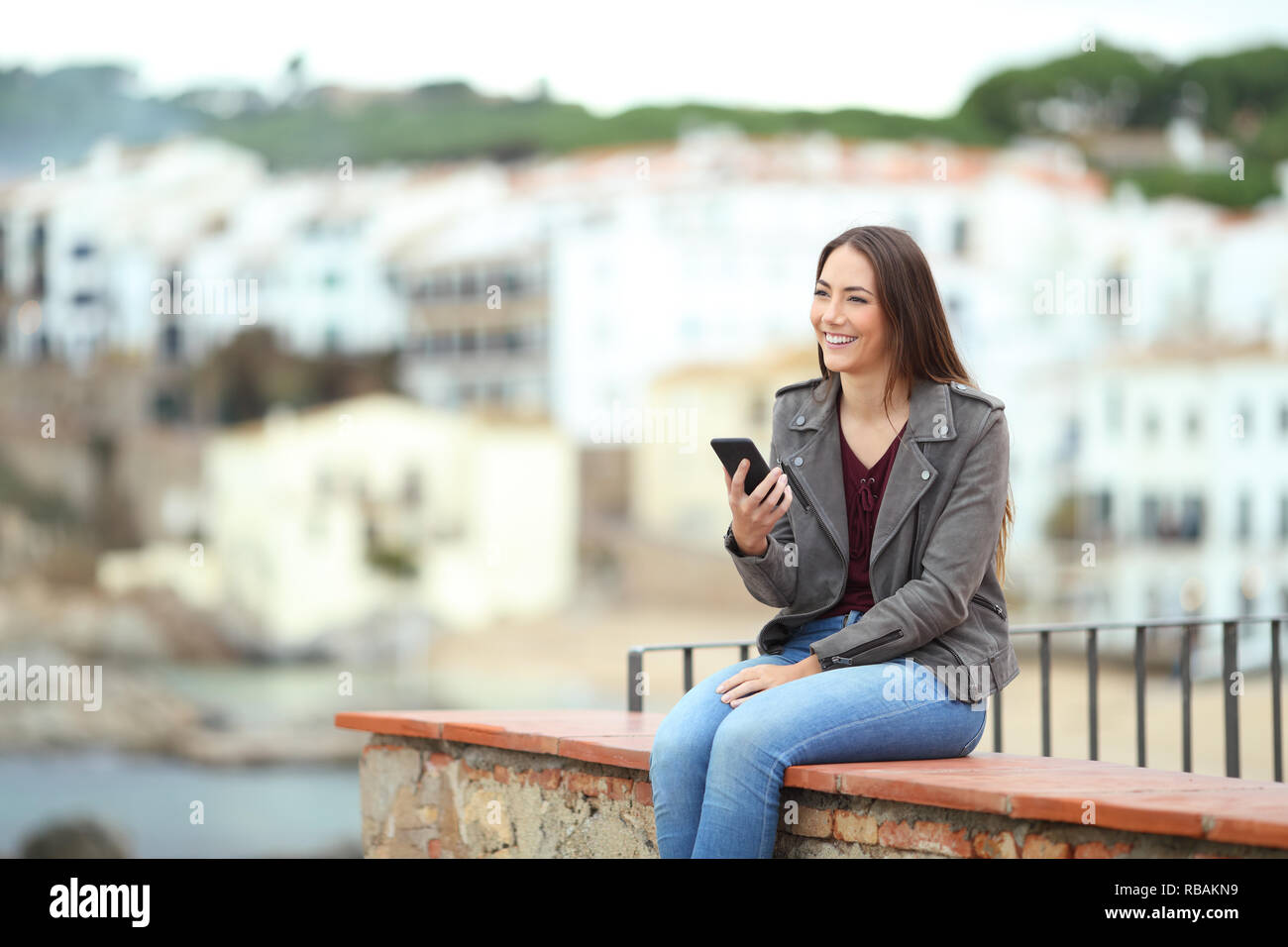 Happy woman holding smart phone contemplating views sitting on a ledge on vacation - Stock Image