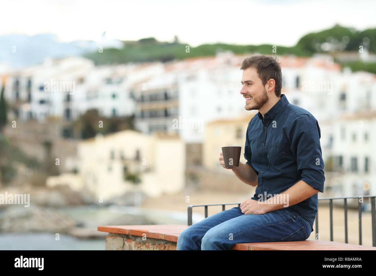 Happy man drinking coffee and looking away sitting on a ledge in a coast town on vacation - Stock Image