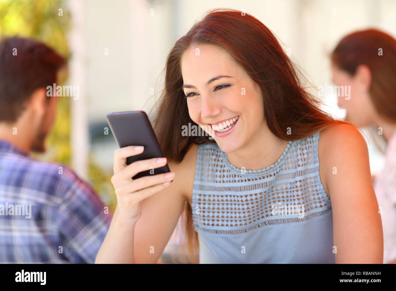 Happy woman reading message on a smart phone sitting in a bar terrace - Stock Image