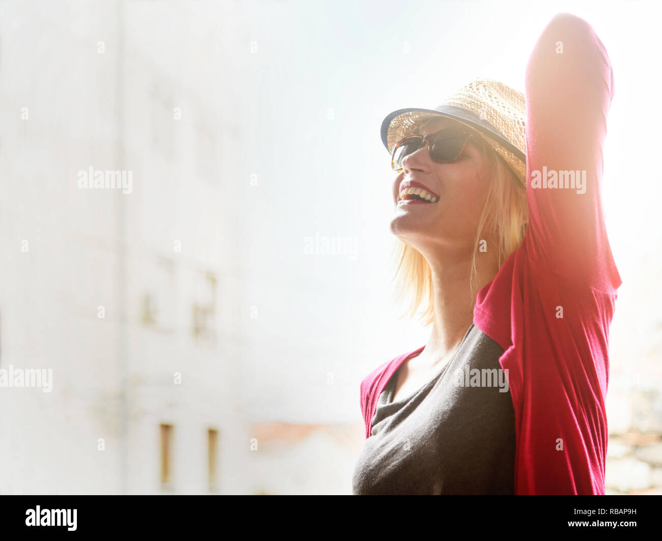 Young happy hipster woman tourist in casual fashion clothing and summer stylish hat traveling and enjoy the summer holiday in the city. Youth lifestyl - Stock Image