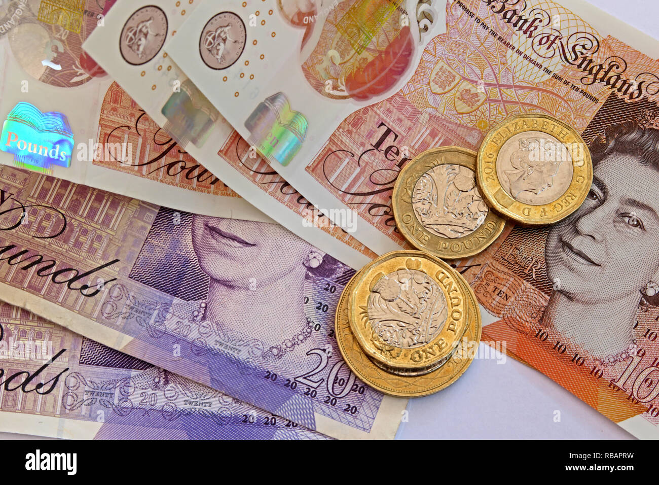 Bank Of England plastic £5 £10 Five pound and ten pound bank notes, with coins - Stock Image