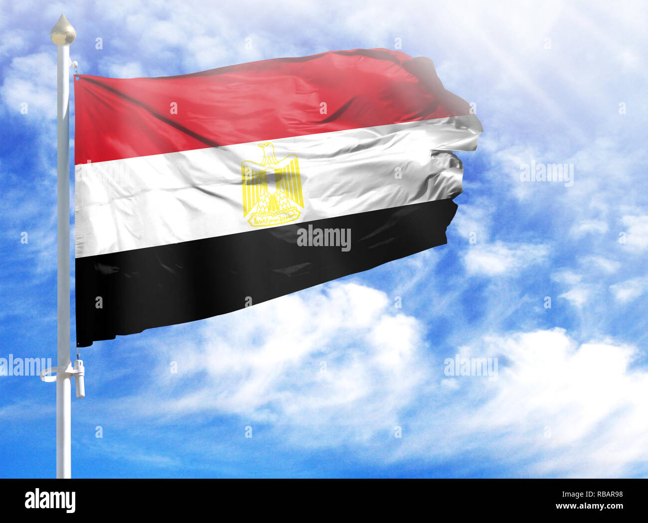 National flag of Egypt on a flagpole in front of blue sky. - Stock Image