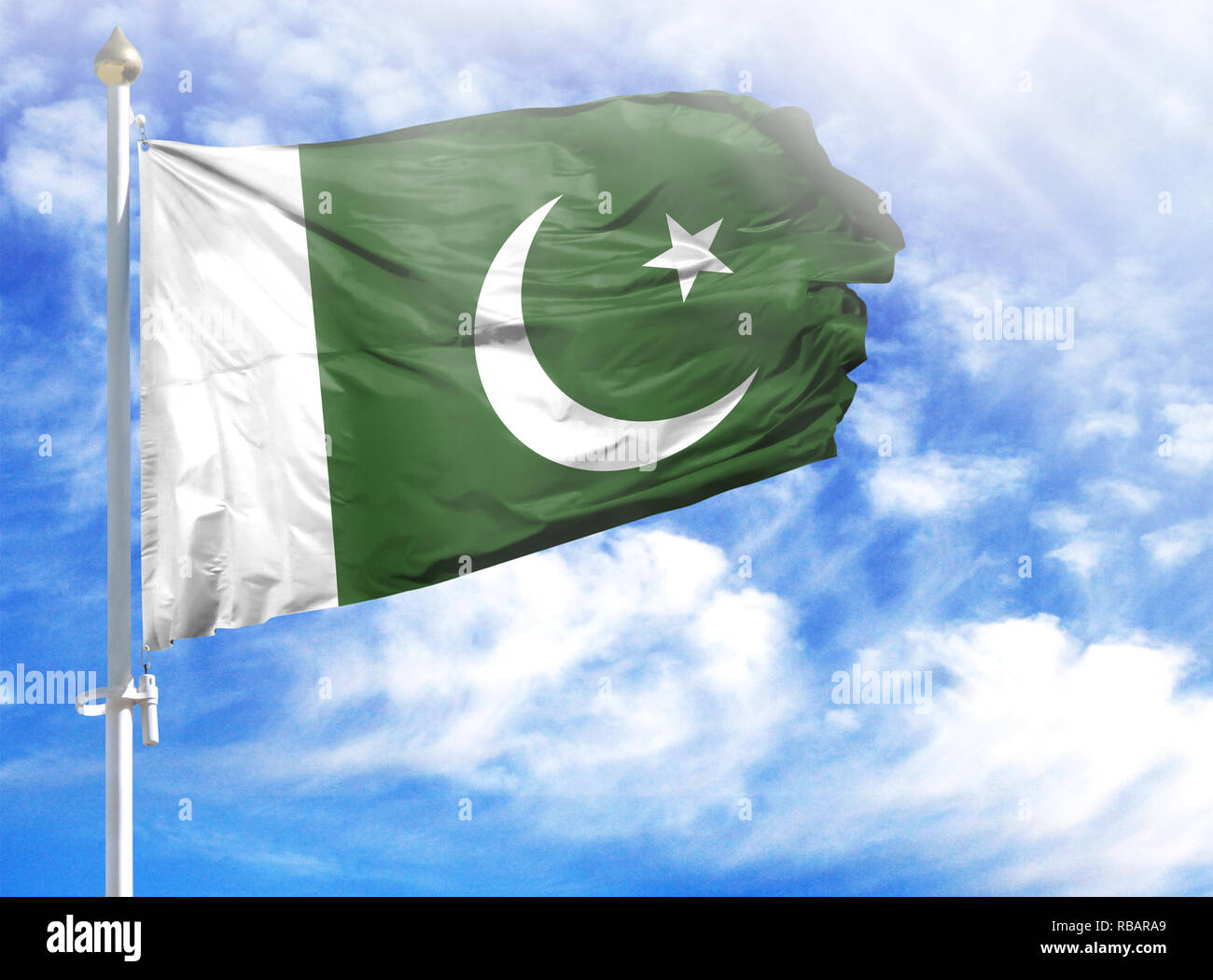 National flag of Pakistan on a flagpole in front of blue sky. - Stock Image