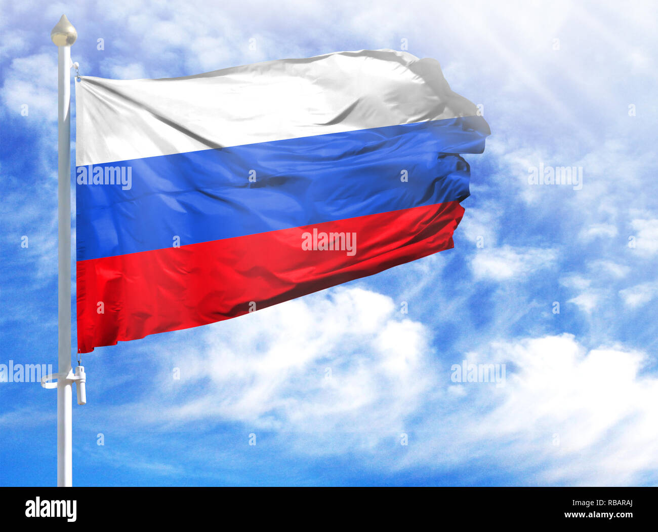 National flag of Russia on a flagpole in front of blue sky. - Stock Image