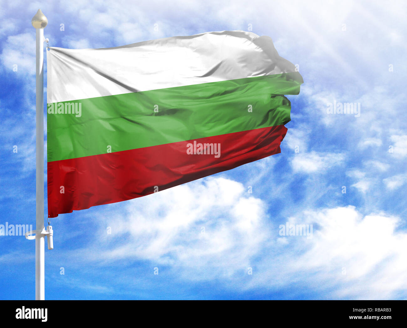 National flag of Bulgaria on a flagpole in front of blue sky. - Stock Image