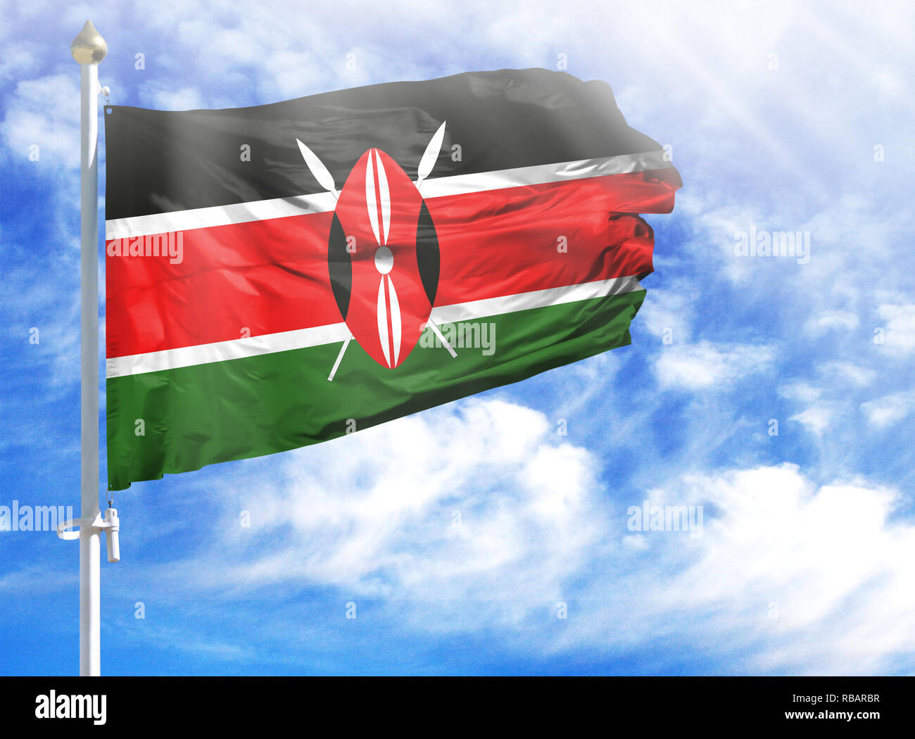 National flag of Kenya on a flagpole in front of blue sky. - Stock Image