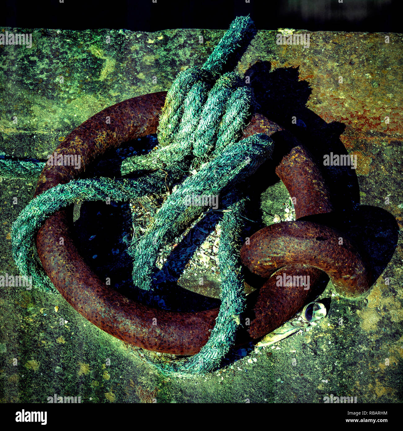 Rope tied around a rusty metal ring - Stock Image