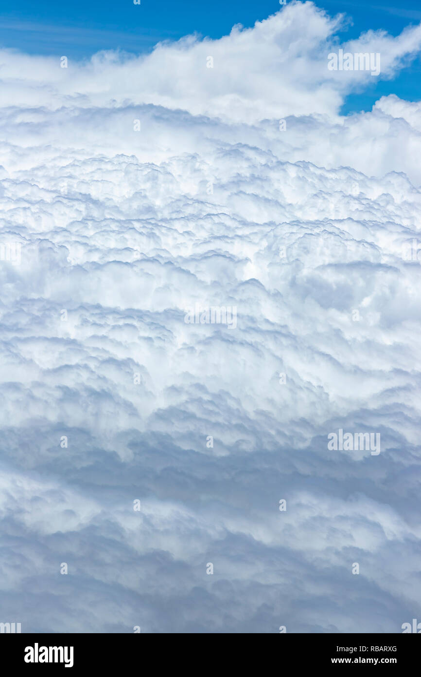 Beautiful view from the window of a plane flying over clouds. Natural panorama with clouds. White clouds moving above the ground. Stock Photo