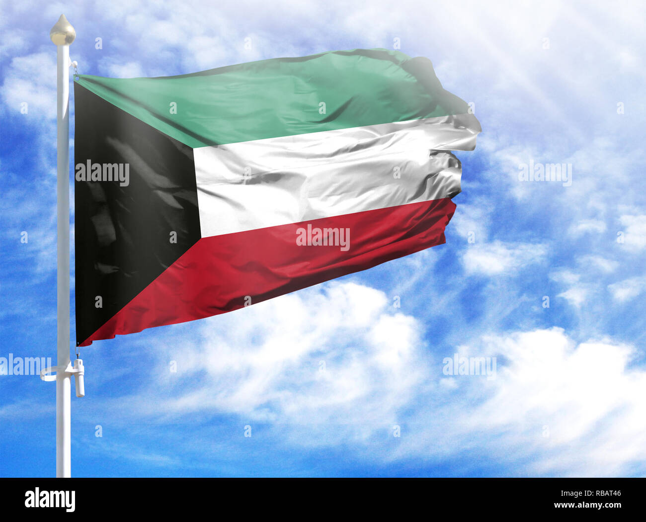 National flag of Kuwait on a flagpole in front of blue sky. - Stock Image