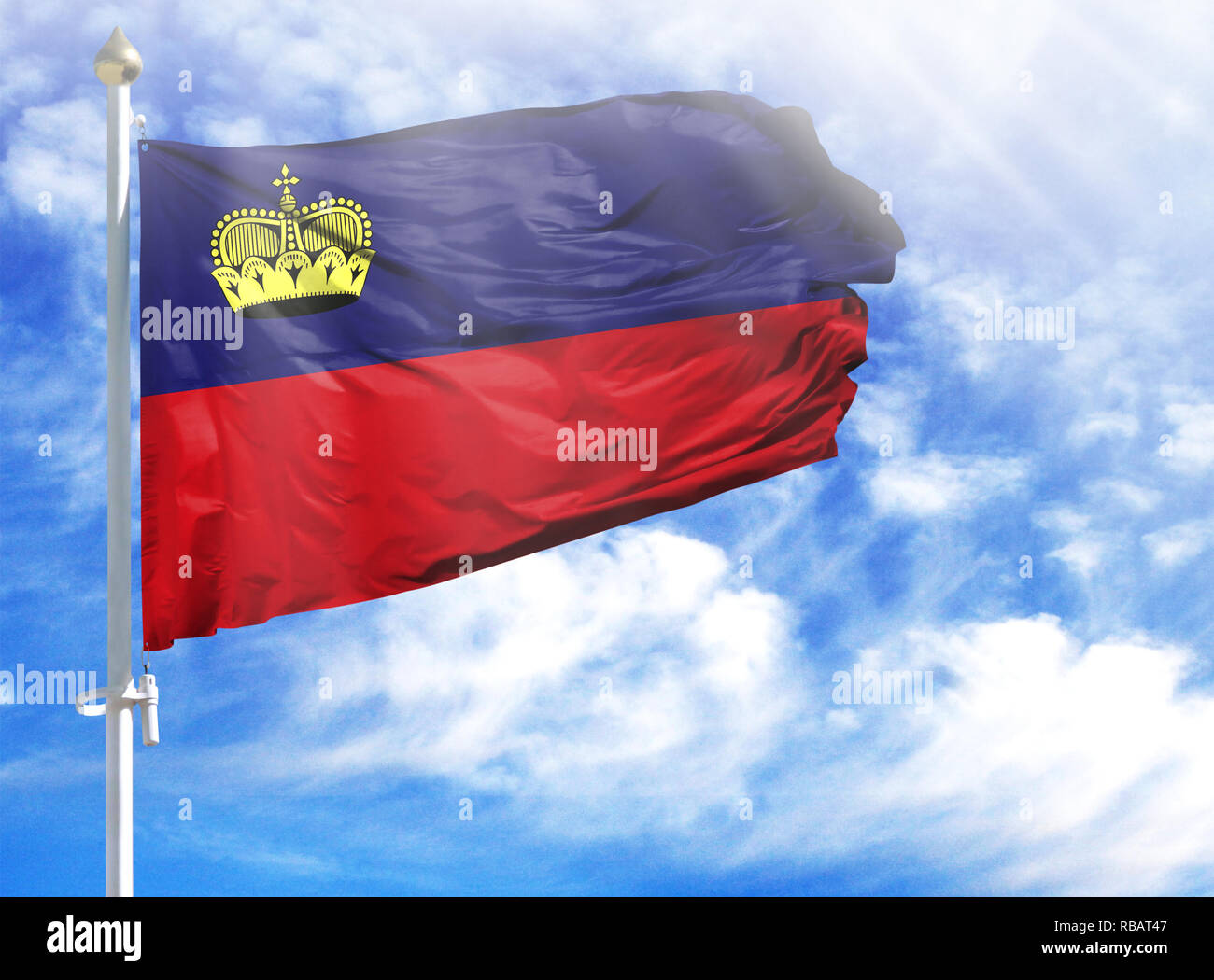 National flag of Liechtenstein on a flagpole in front of blue sky. - Stock Image