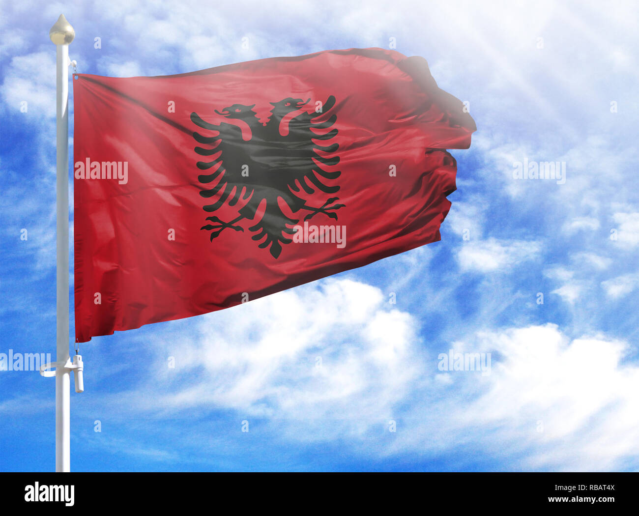 National flag of Albania on a flagpole in front of blue sky. - Stock Image