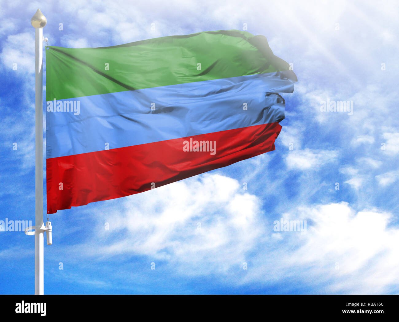 National flag of Dagestan on a flagpole in front of blue sky. - Stock Image
