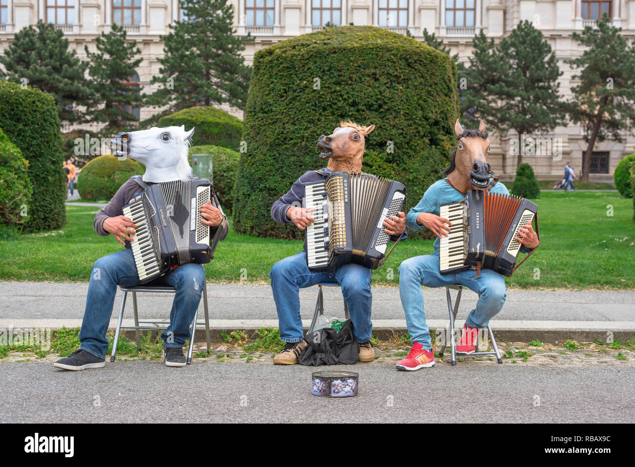 Buskers street entertainment, a trio of accordionists wearing bizarre headgear play for passersby in Maria Theresienplatz, Vienna, Wien, Austria. - Stock Image