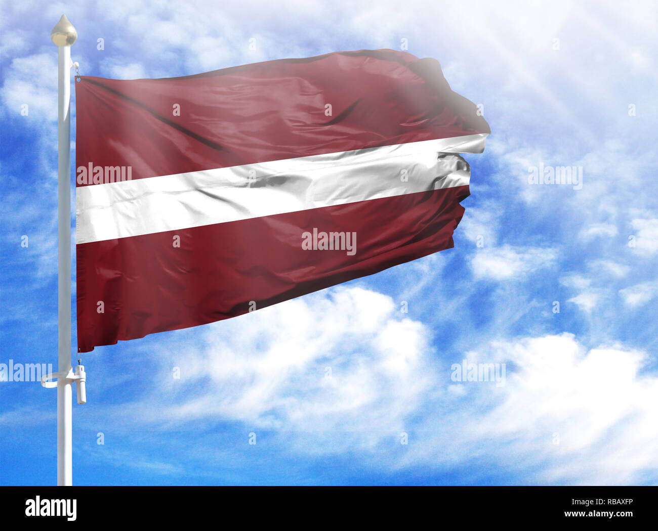 National flag of Latvia on a flagpole in front of blue sky. - Stock Image