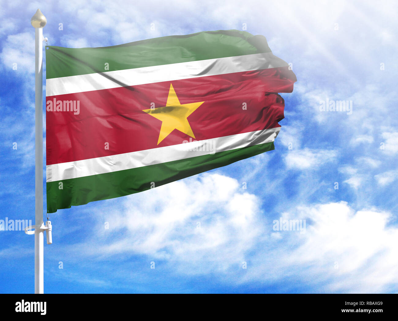 National flag of Suriname on a flagpole in front of blue sky. - Stock Image