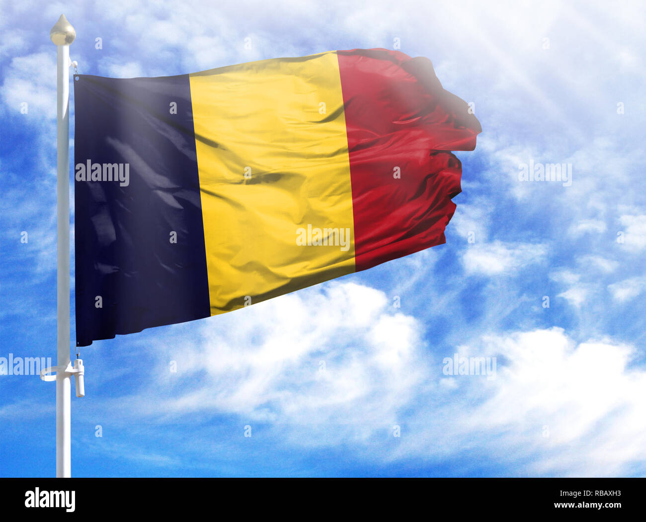 National flag of Chad on a flagpole in front of blue sky. - Stock Image