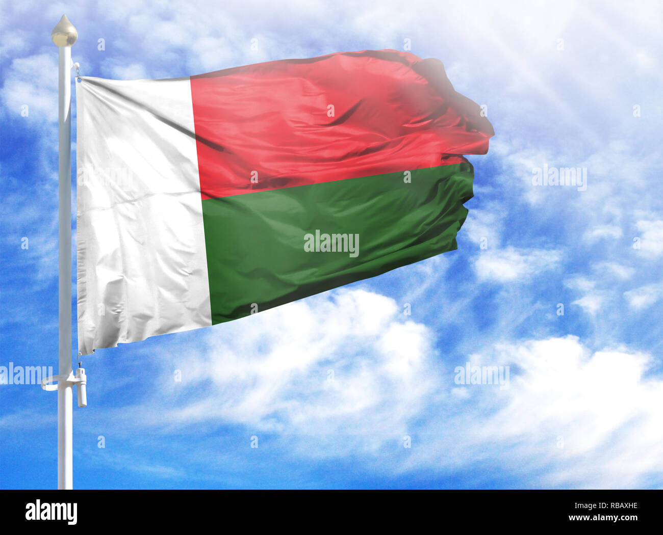 National flag of Madagascar on a flagpole in front of blue sky. - Stock Image