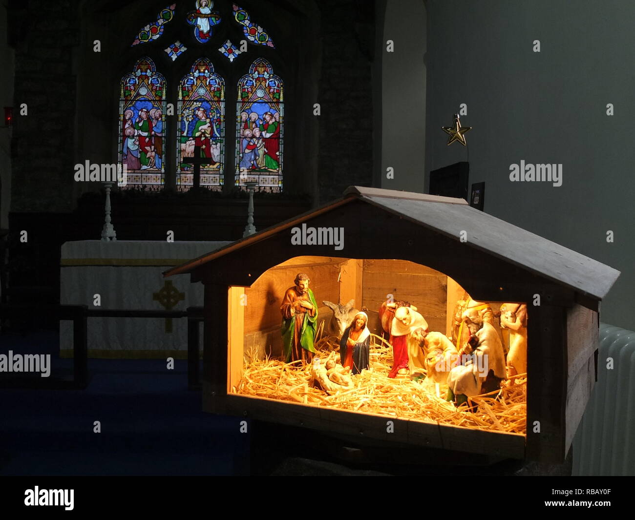 Illuminated crib nativity scene in a church for Christmas (St Edmunds Church, Castleton, Derbyshire, UK) Stock Photo
