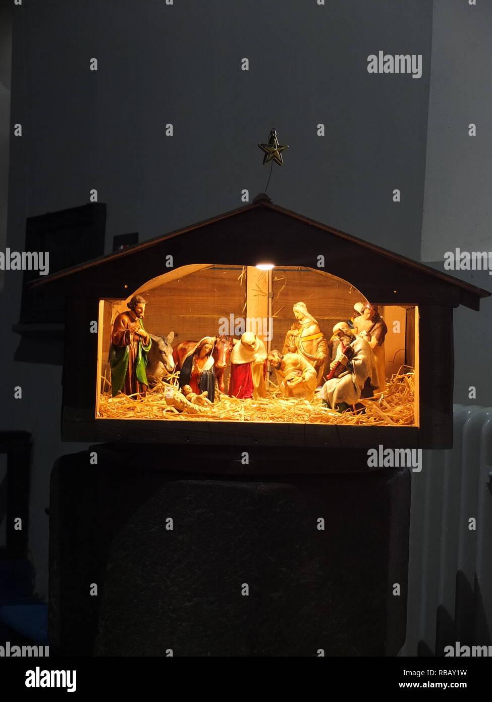 Illuminated crib nativity scene in a church for Christmas (St Edmunds Church, Castleton, Derbyshire, UK) Stock Photo