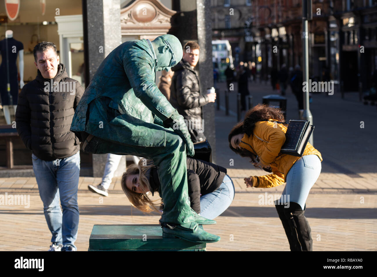 Two women trying to work out how a street performer is levitating,Leeds,West Yorkshire,England,UK. - Stock Image