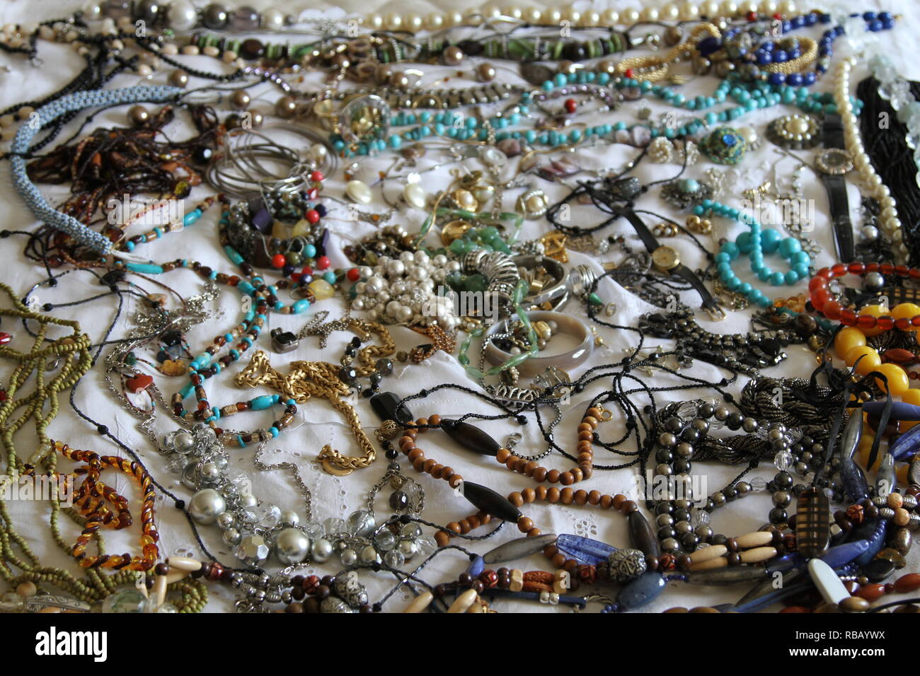 Jewellery. A collection of jewellery laid out on a bed with a white sheet. Jewells. Valuables. Personal property. Sentimental value. Stones. Pearls. Beads. Necklaces. Bracelets. A wrist watch. Multi coloured. Assortment. Stock Photo