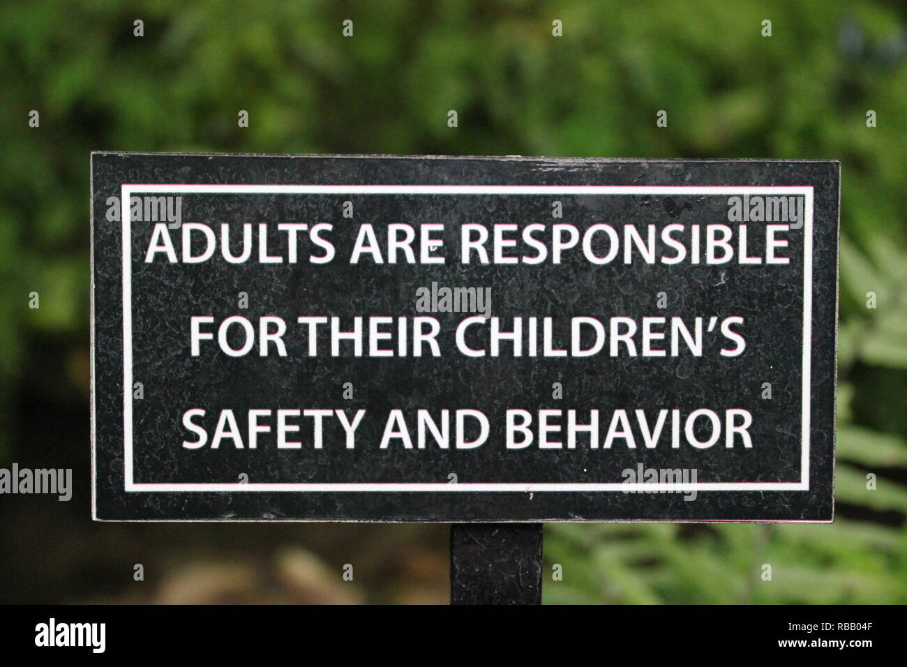 Adults are responsible for their children's safety and behavior sign posted at the Christmas Holiday flower Show at the Lincoln Park Conservatory in Chicago, Illinois, USA. - Stock Image