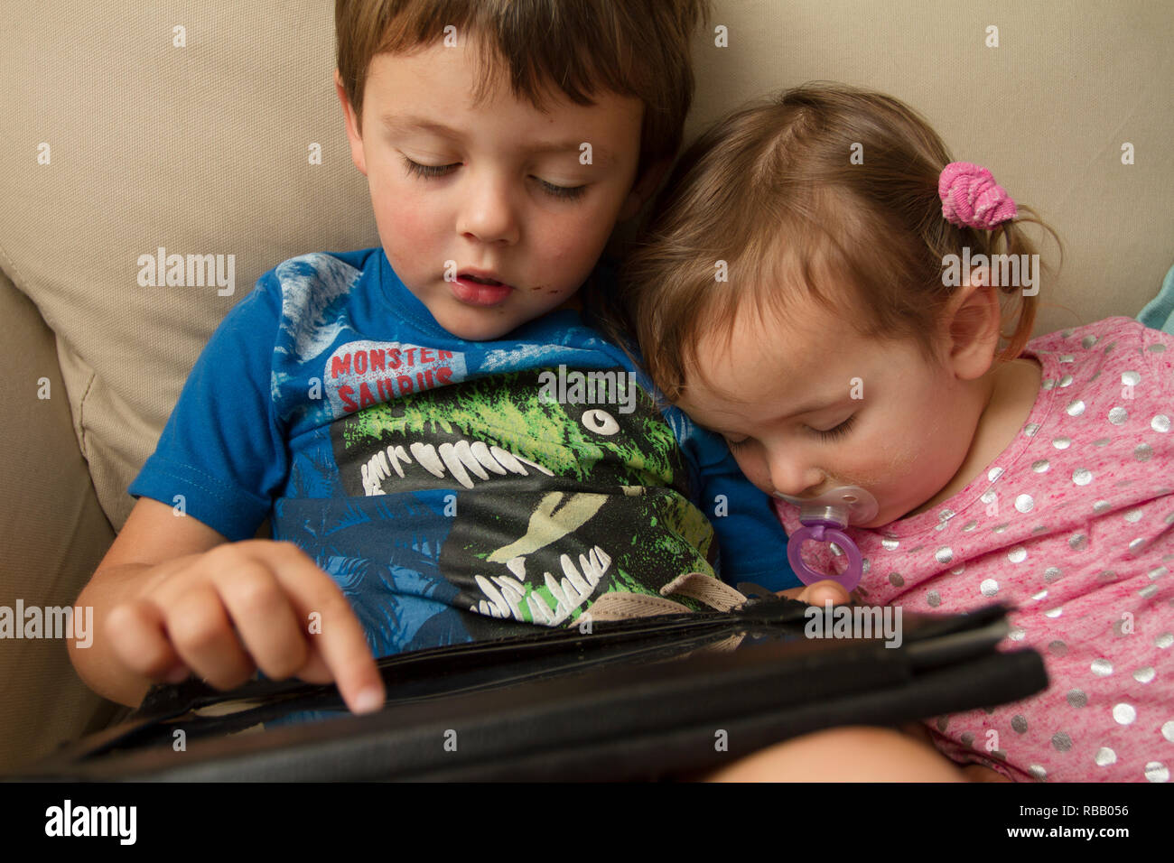 Little boy plays on iPad while his little sister is sleeping next to him - Stock Image