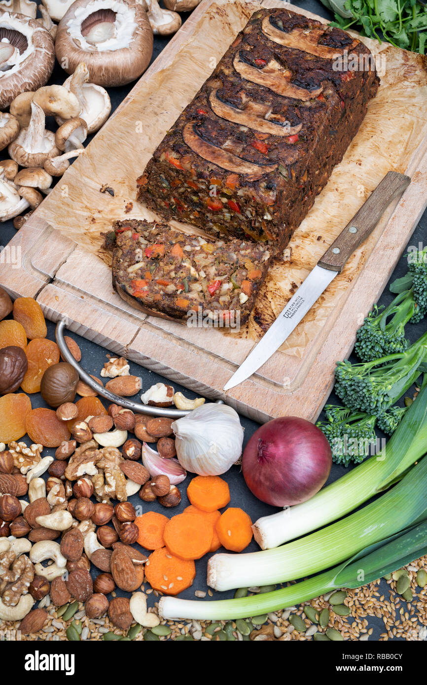 Vegan nut roast / nut loaf on a wooden board with ingredients and a vintage kitchen knife from above. UK - Stock Image